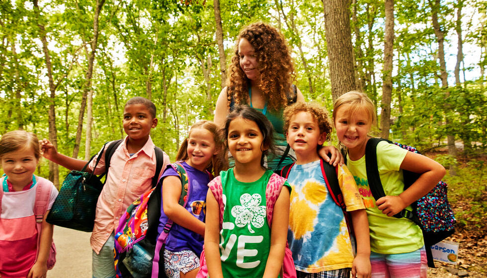 Group of children standing in the woods smiling.