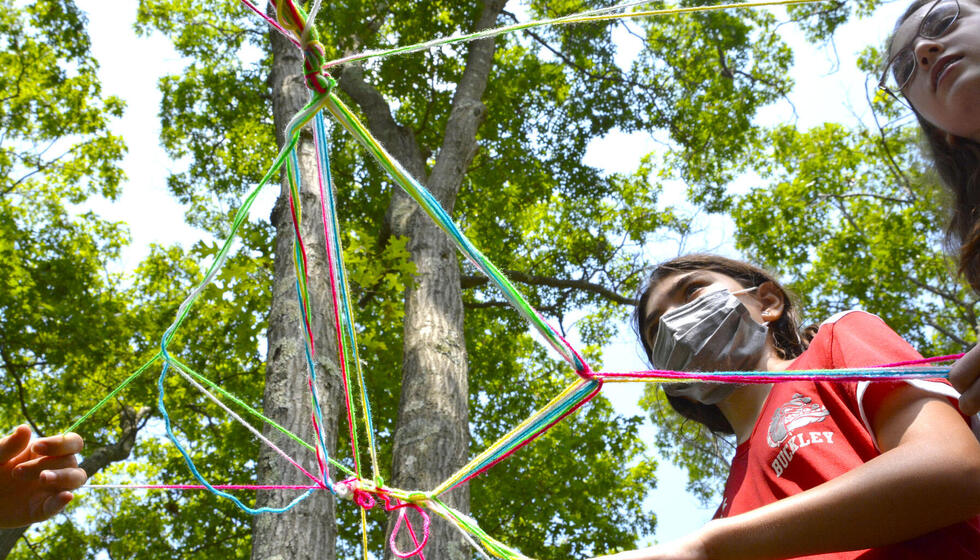 Students standing under yarn sculpture.