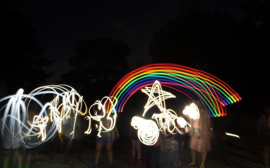 Children in the dark using lights to make shapes with light and motion. We see a rainbow and a star and squiggles.