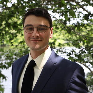 Smiling man with glasses in a suit.