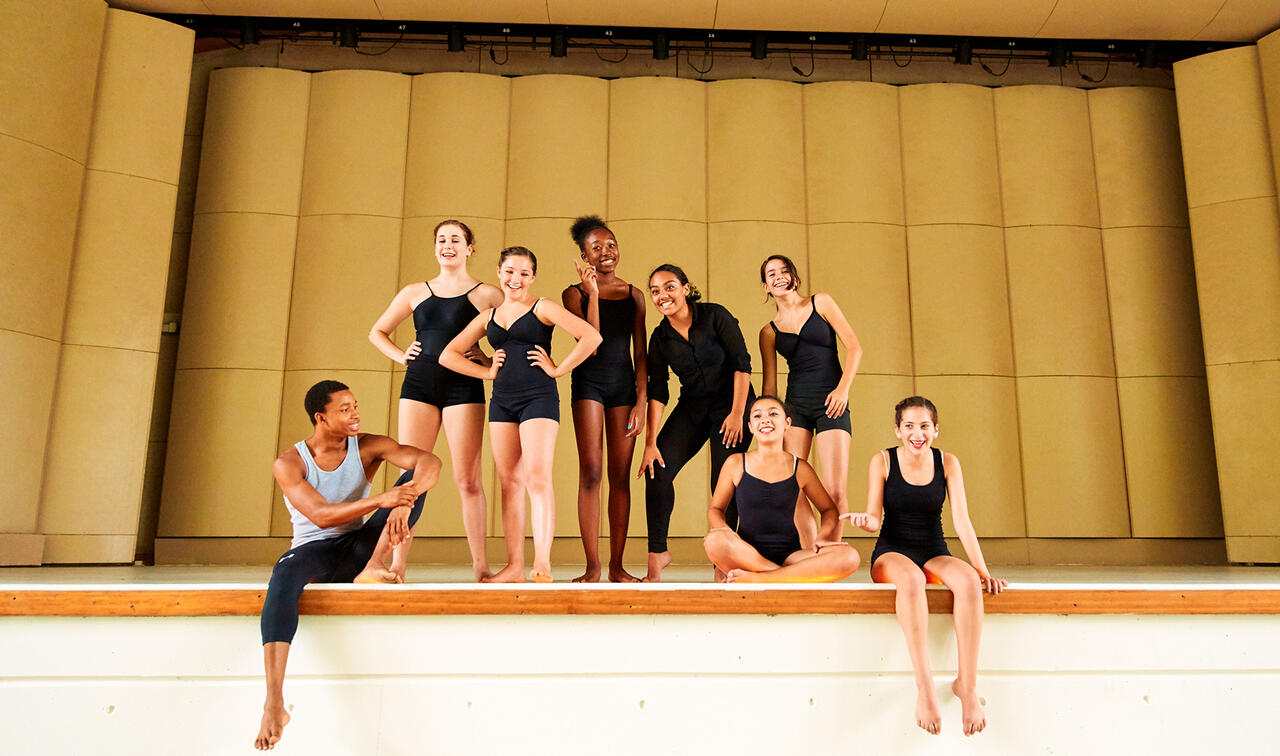 Dancers sitting on stage and smiling