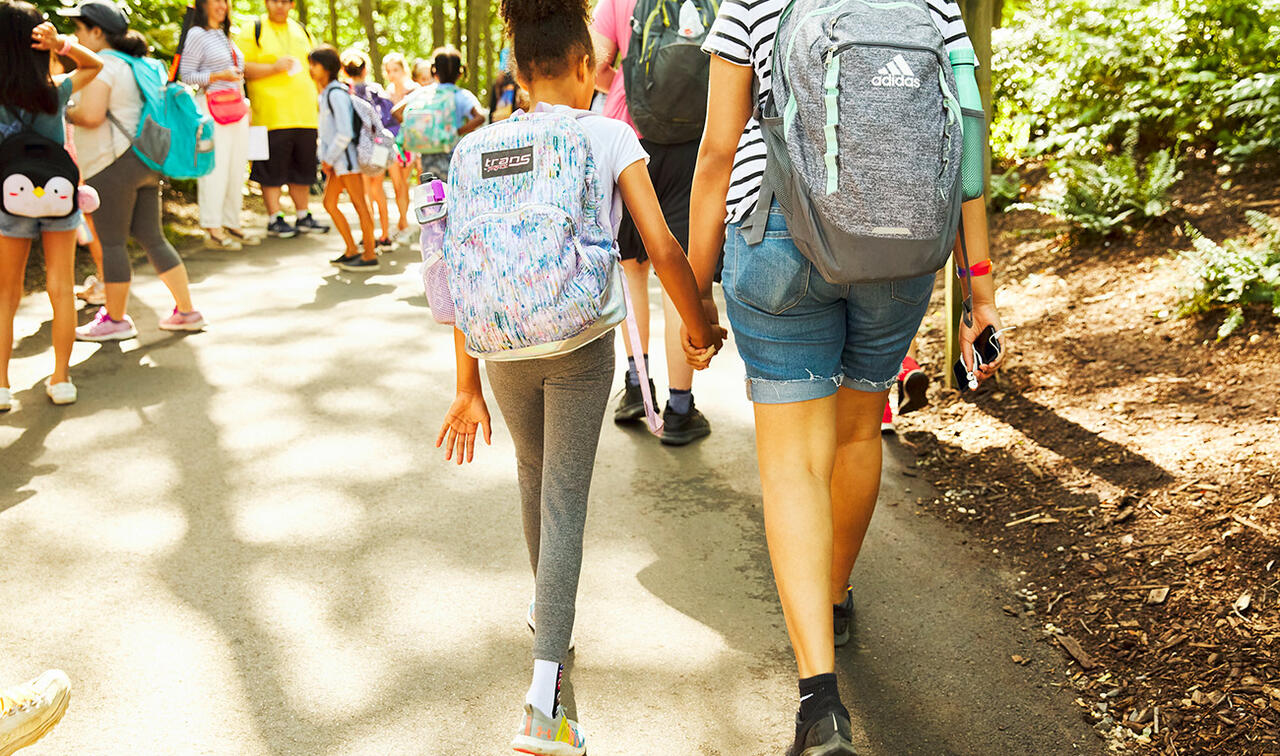 Two campers with backpacks walking and holding hands