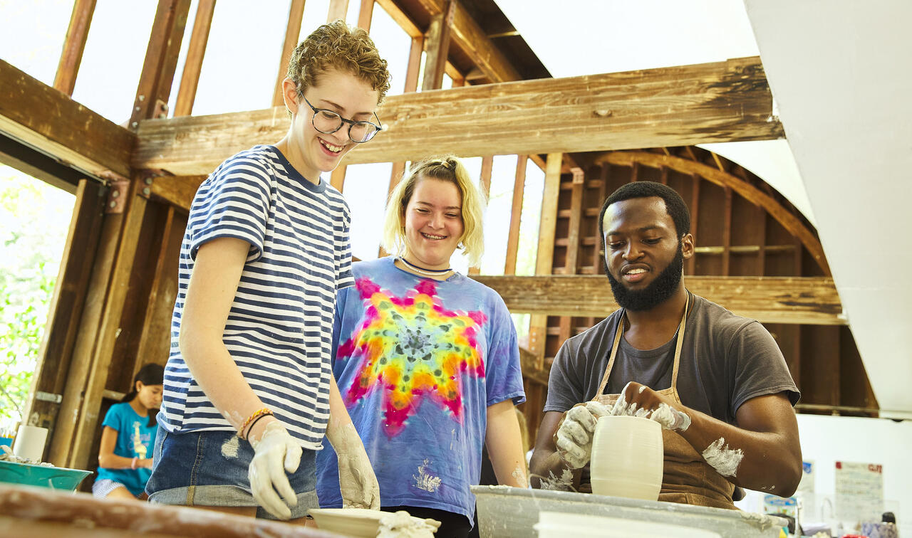 Two smiling art students stand next to the seated ceramics teacher who is working on a pot.
