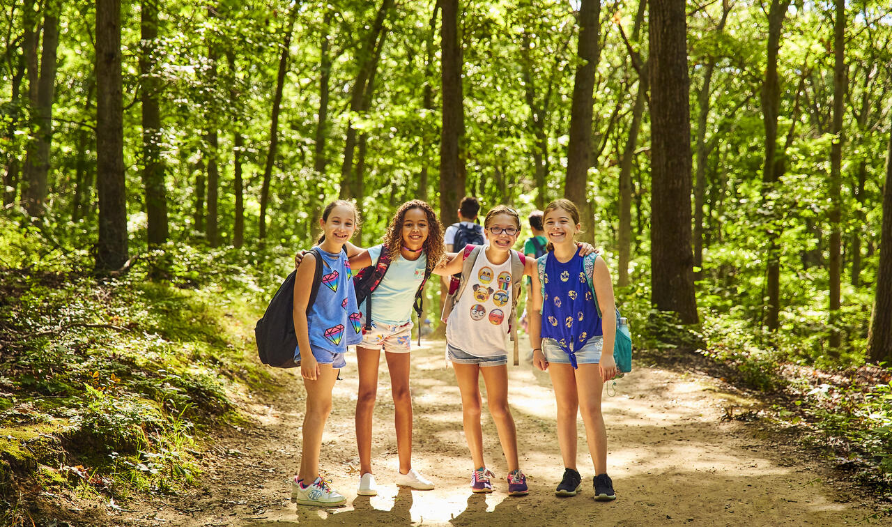 Group of four girls standing on a sunny woodland path, smiling.