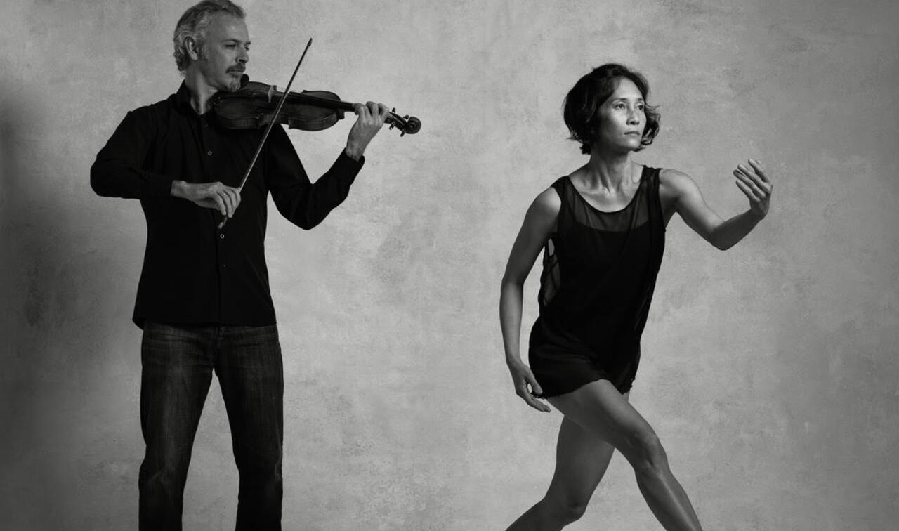 Black and white photo of violinist playing and dancer moving towards the shot in dancers pose.