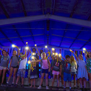 Children standing on stage holding lights and waving them in the air.