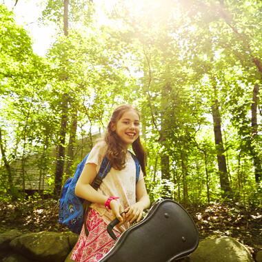 Girl in the woods holding a violin.