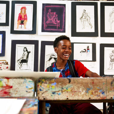 Young boy sitting at an art studio desk smiling with paintings pinned up behind him.