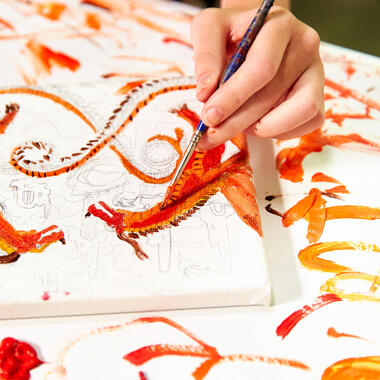 Closeup of child's hand painting an orange dragon on canvas.