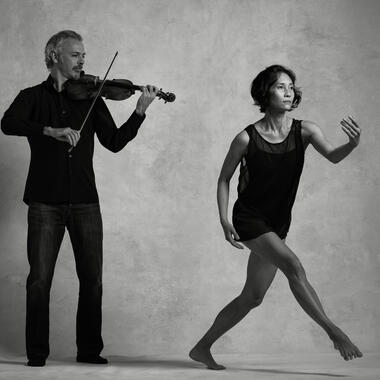 Black and white photo of Colin Jacobsen emotionally playing the violin and Maile Okamura mid-movement.